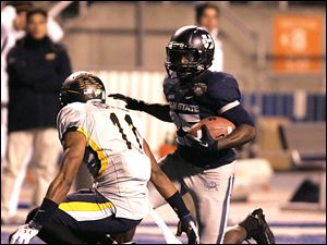 Utah State's Kerwynn Williams (25) rushes for a first down against Toledo's Cheatham Norrils.