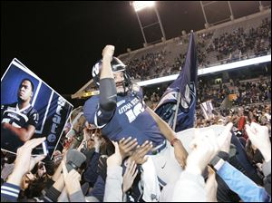 Utah State's Chuckie Keeton celebrates with teammates and fans after defeating Toledo at the Famous Idaho Potato Bowl.