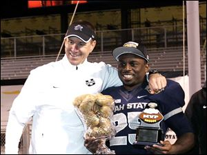 Utah State head coach Gary Andersen smiles as Kerwynn Williams holds up the MVP award and the aowl game trophy.