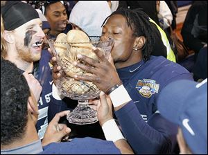 Utah State's Nevin Lawson celebrates by kissing the Famous Idaho Potato Bowl trophy.