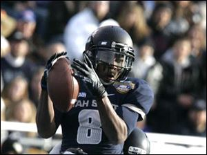 Utah State's Travis Reynolds makes a reception against Toledo's Joey DeMartino.