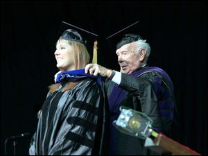 Kristine R. Angevine is hooded by her grandfather, Robert Willenbrink. Angevin received a PhD in Biomedical Science in Cardiovascular and Metabolic Diseases.