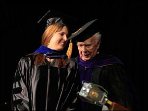 Kristine R. Angevine is hooded by her grandfather, Robert Willenbrink. Angevin received her PhD in Biomedical Science in Cardiovascular and Metabolic Diseases.