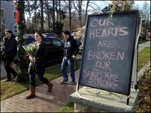 A chalked sign outside a downtown business reflects the emotions in Newtown, Conn., after the massacre. Similar signs have sprung up throughout the city of 26,000.