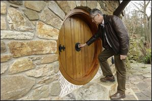 Architect Peter Archer enters the Hobbit house by opening a knob in the center, just as J.R.R. Tolkient described. Mr. Archer and his team designed th