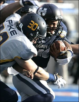 Utah State's Chuck Jacobs runs against the defense of Toledo's Ben Pike today in Boise, Idaho.
