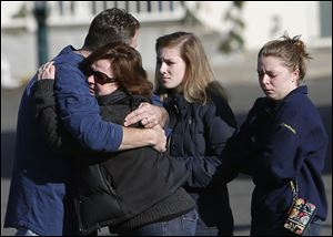Mourners embrace outside Saint Rose of Lima Roman Catholic Church on Saturday.