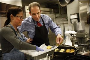 Rabbi Sam Weinstein helps Deborah Dolin, religious education director at Temple Shomer Emunim, make latkes in the temple kitchen.