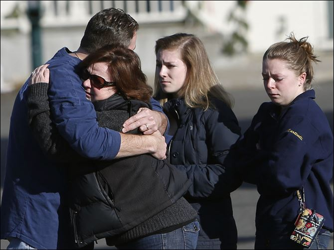 Mourners embrace outside Saint Rose Mourners embrace outside Saint Rose of Lima Roman Catholic Church on Saturday.