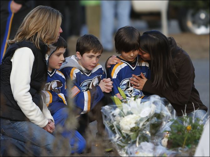 From left, Jean Bradley, Steven Turchetta, 9, Jean's son Matthew Bradley, 9, Ashton Baltes, 10, and his mother Elonda Baltes pay their respects today at a memorial for shooting victims near Sandy Hook Elementary School.