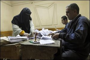 Egyptian referendum officials count votes at a polling station in Cairo, Egypt, late Saturday.