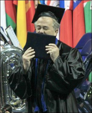 Paul Manol of Sylvania kisses his diploma after graduating magna cum laude with a bachelor of science degree from UT's college of lifelong learning.