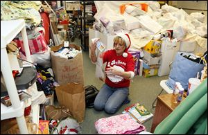 Volunteer Kim Fisher sorts through toys before a Christmas party at Helping Hands of St. Louis in Toledo.