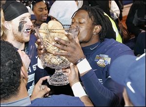 Utah State's Nevin Lawson celebrates by kissing the Famous Idaho Potato Bowl trophy after defeating the University of Toledo. The Rockets were stymied mainly by the Aggies' defense.