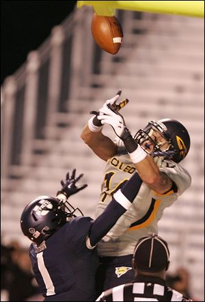 Toledo's Justin Olack, top, tries to pull down a reception against Utah State's Nevin Lawson.