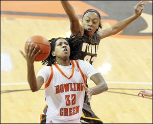 BGSU's Alexis Rogers takes the ball to the hoop past Wyoming's Chaundra Sewell during the first half of women's basketball action at the Stroh Center on Saturday. The Falcons won 79-69.