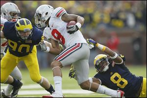 Michigan cornerback J.T. Floyd, right, has been suspended along with linebacker Brandin Hawthorne and punter Will Hagerup for the Outback Bowl for a violation of team rules.
