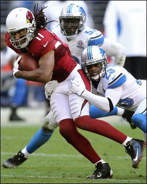 Arizona Cardinals wide receiver Larry Fitzgerald (11) is tackled by Detroit Lions cornerback Chris Houston (23) during the second half of their game in Arizona. The Cardinals won 38-10.