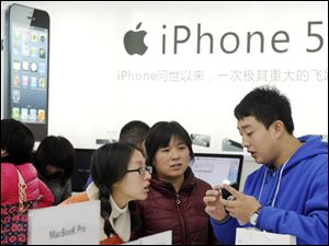 A storekeeper introduces iPhones to customers near an iPhone 5 advertisement at an Apple products shop in Dongyang, in eastern China's Zhejiang province, Friday.