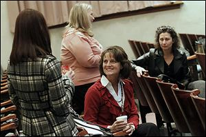 Kelly Sell, left, and Lisa Richard, center, join other members in chatting before the Downtown Perrysburg Inc. annual general membership meeting at the Auditorium of the Perrysburg Schools Board of Education building in Perrysburg. The group met to review 2012 accomplishments and preview 2013 plans.