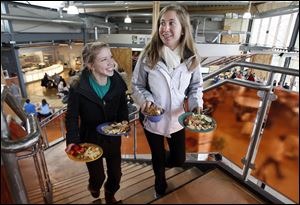 Shannon Cassidy, left, and Amber Herron, both 19-year-old freshmen at BGSU, carry their food to a table at the Oaks dining hall. It and Carillon Place lack the cafeteria trays
