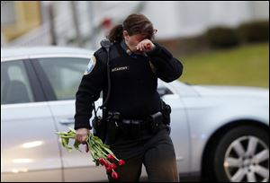 Newtown Police Officer Maryhelen McCarthy carries flowers near a memorial for shooting victims Sunday, Dec. 16, 2012 in Newtown, Conn.  A gunman walked into Sandy Hook Elementary School in Newtown, Friday and opened fire, killing 26 people, including 20 children. The flowers and other items were taken to nearby Saint Rose of Lima Roman Catholic Church.