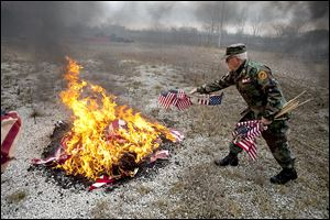 Larry Barnett of the Marine Corps League Lou Diamond Detachment #272 throws a handful of U.S. flags into the fire, the correct way to dispose of flags.