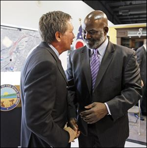 Ohio Gov. John Kasich, left, speaks with Toledo Mayor Mike Bell after announcing plans for the Ohio Turnpike, and future funding of Ohio highway projects, during a news conference at Modern Builders Supply in Toledo on Thursday.