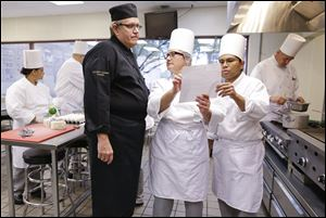 Chief instructor Larry Baumann, left, answers questions for students in a professional cook class at the Culinary Academy of Las Vegas.