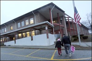 Manuel Moreno, right, walks his daughter Jady, 6, to the Morris Street elementary school in Danbury, Conn.