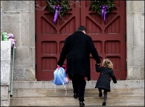 A man helps a young girl up the stairs while carrying her backpack as they arrive for services at Trinity Church in Newtown, Conn., on Sunday.