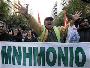 Striking Greek municipal employees chant slogans during a protest outside at the northern port city of Thessaloniki, Greece as a banner reads in Greek