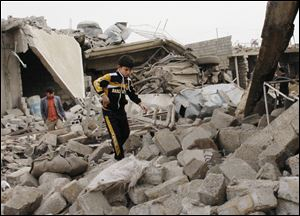 A boy walks in rubble at the scene of a car bomb attack in al-Mouafaqiyah, a village inhabited by families from the Shabak ethnic group, near the city of Mosul, 225 miles northwest of Baghdad, Iraq.