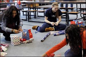 Grisoranyel Barrios, 17, left, jokes with Carolyn Manley, 17, center, as the pair join their classmates in wrapping presents for children at Providence Lutheran Church in  Springfield Twp.