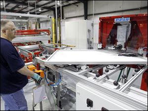 Production worker Kevin Morris uses a machine to crimp the corners of a 250 watt solar panel frame at Isofoton.