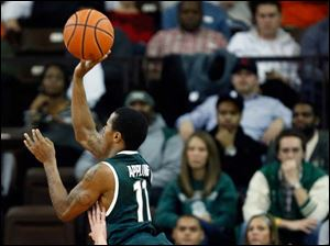 Michigan State guard Keith Appling charges over Bowling Green State University guard Luke Kraus.