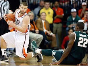 Bowling Green State University guard Luke KrauS knocks over Michigan State guard Branden Dawson.