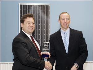 Tom Kimbis of the Solar Energy Industries Association, left, presents an award as America's Number One Solar Small Town to Napoleon mayor Ron Behm at Isofoton.