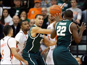 Michigan State guard Denzel Valentine looks for an opening as Bowling Green defenders close in.