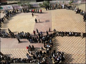 Egyptians wait in line to cast their votes during a referendum on a disputed constitution drafted by Islamist supporters of President Morsi in Cairo, Egypt, Saturday.