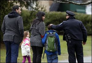 Easton police officer J. Sollazzo greets a returning student as he is walked into Hawley School, today in Newtown, Conn.