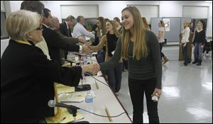 Board member Gretchen Downs shakes the hand of Perrysburg girls soccer player Andrea Wertz during Perrysburg school board meeting at the Commodore Building in Perrysburg, Ohio.