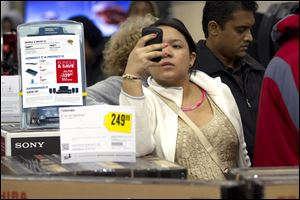 A shopper at a Florida Best Buy checks her smart phone. More retailers are plumbing social media sites such as Facebook to learn what their customers want to see on store shelves.