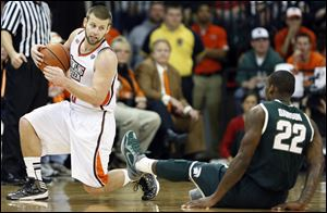 Bowling Green State guard Luke Kraus, left, knocks over Michigan State guard Branden Dawson on Tuesday night.