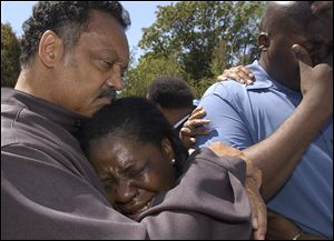 The Rev. Jesse Jackson comforts relatives of crash victim Terrance Shurn, whose death sparked rioting. Alma White, center, is Mr. Shurn's aunt, and Shannon Shurn is his brother.