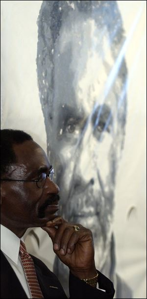 Rubin 'Hurricane' Carter, a former boxer who was found guilty of murder in 1967 but later released because the conviction was  racially motivated, waits to speak in St. Joseph, Mich. He said residents of nearby Benton Harbor need to be heard to stop the violence there. Mr. Carter also questioned the need for extra police, which he likened to an 'occupation' force.