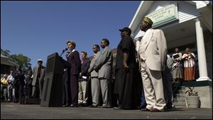 Michigan Gov. Jennifer Granholm, backed by community leaders, addresses local concerns outside a Benton Harbor church.