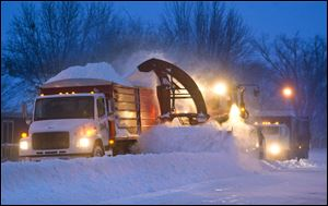Crews in Pine Island, Minn., were out early clearing roads before commuters headed to work as the first big snowstorm of the season struck Thursday.