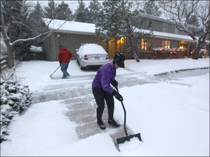 A woman and her husband shovel their A woman and her husband shovel their walk as a blizzard dropped snow over Boulder, Colo. on Wednesday.