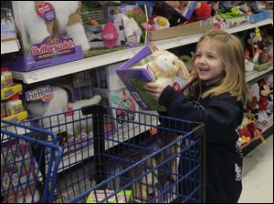 Kadence Fowler, 5, holds a bunny she found on the shelf.